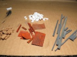 Various bits. 'Metal' scraps (mostly plastic in fact), wood planks (balsa), and bricks/rocks made of foam and cork.