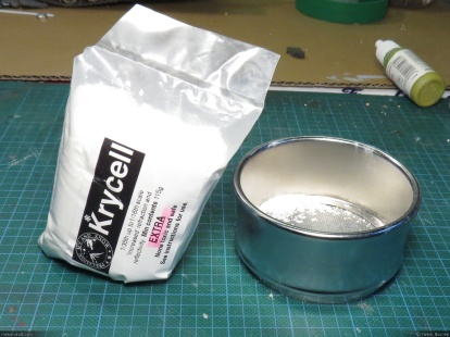 A bag of Krycell Snow and the stainless steel sieve