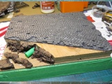 """I removed some individual stones from the road to damage it. Then pieces of cork were glued on the """"crater"""" part of the diorama."""