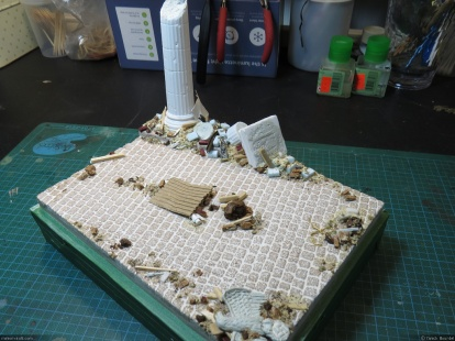 Various debris are then glued to the base using white glue and wood filler.